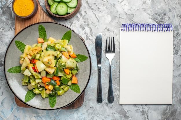 暗い背景のまな板フォークナイフメモ帳の楕円形プレート上の上面図グリーントマトサラダ