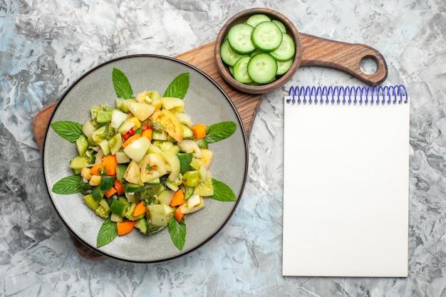 暗い背景のまな板ノートブックの楕円形プレート上の上面図グリーントマトサラダ