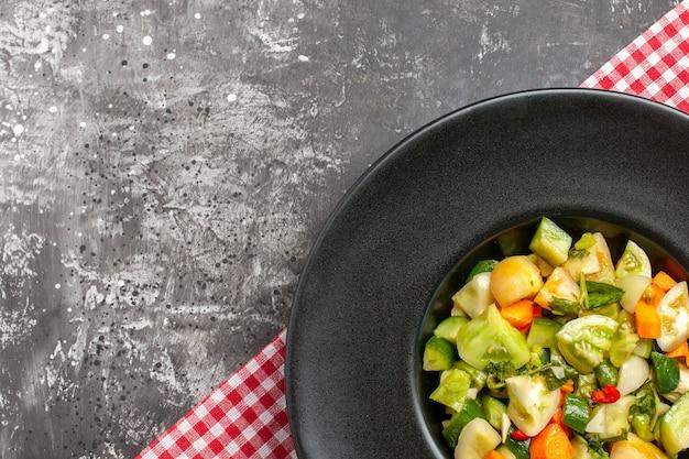 暗い背景の楕円形のプレートにグリーントマトサラダの上面図
