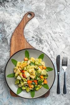 暗い背景の上のフォークナイフのサービングボード上の楕円形のプレート上の上面図グリーントマトサラダ