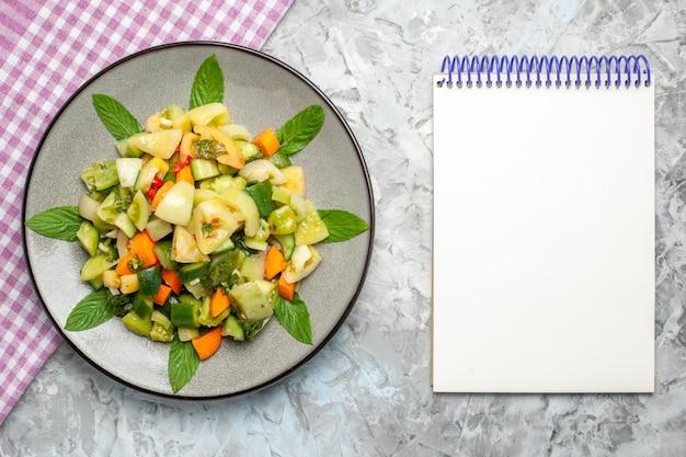 灰色の背景に楕円形のプレートピンクのテーブルクロスのメモ帳にトップビューグリーントマトサラダ