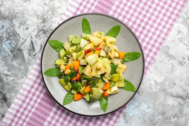 灰色の背景に楕円形のプレートピンクのテーブルクロスの上面図グリーントマトサラダ