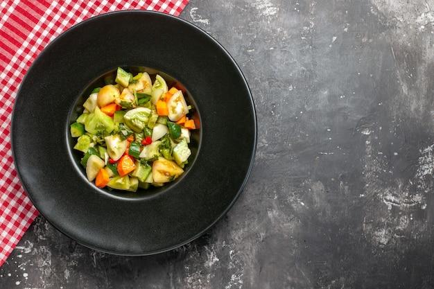 어두운 표면에 타원형 접시 빨간색 식탁보에 상위 뷰 녹색 토마토 샐러드
