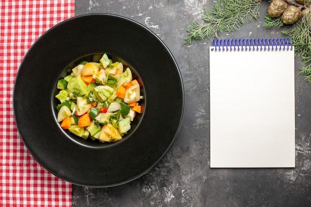 타원형 접시에 있는 상단 보기 녹색 토마토 샐러드 빨간색 흰색 체크 무늬 식탁보 어두운 표면에 노트북