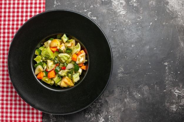 어두운 표면에 타원형 접시 빨간색 흰색 체크 무늬 식탁보에 상위 뷰 녹색 토마토 샐러드