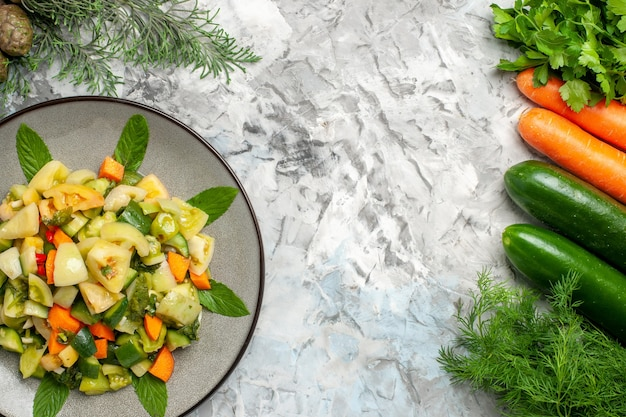 Вид сверху салат из зеленых помидоров на овальной тарелке с овощами на темном фоне