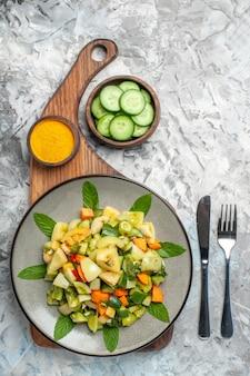 Insalata di pomodori verdi vista dall'alto su piatto ovale su tagliere forchetta e coltello su sfondo scuro