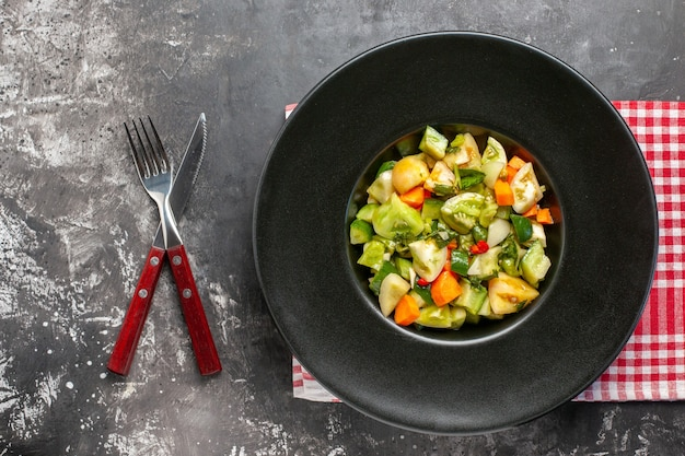 Top view green tomato salad on oval plate crossed knife and a fork on dark background