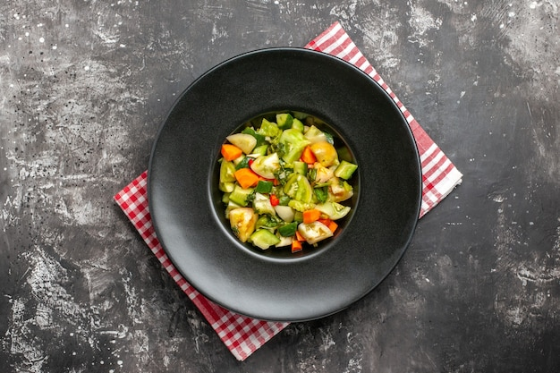 Insalata di pomodori verdi vista dall'alto su piatto ovale su tovagliolo su sfondo scuro
