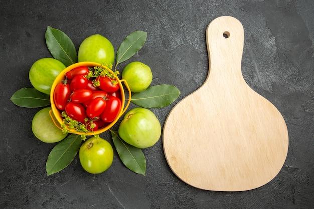 上面図グリーントマトと月桂樹の葉チェリートマトのバケツと暗い表面のまな板