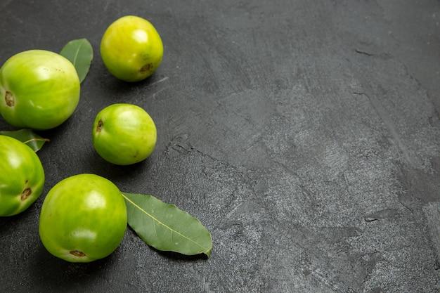 コピースペースのある暗い地面の左側にあるトップビューの緑のトマトと月桂樹の葉