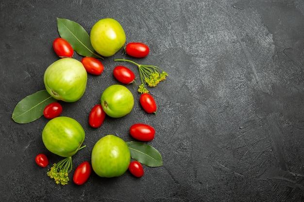 상위 뷰 그린 토마토와 체리 토마토 딜 꽃과 복사 공간이 어두운 땅에 베이 잎