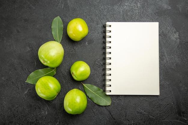 上面図の緑のトマトの月桂樹の葉と暗い表面のノートブック
