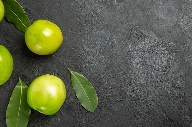 暗い表面の左側にある上面図の緑のトマト月桂樹の葉