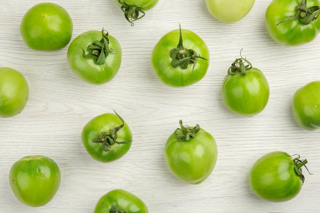 Top view green tomatoes on a light white background