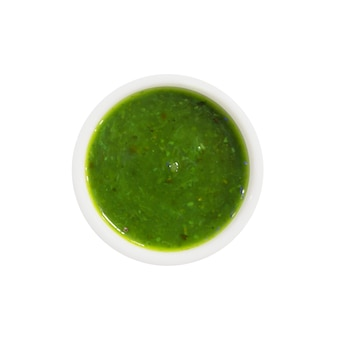 Top view of green vegetable or fruit sauce or jam in round bowl isolated on white background