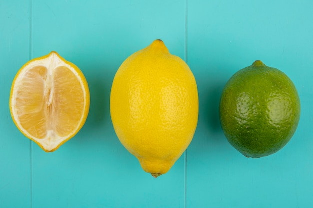 Top view of green an yellow halved and whole lemon with green lime on blue surface