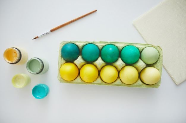 Top view of green and yellow hand painted easter eggs in crate arranged in minimal composition with paint brush on white background, copy space