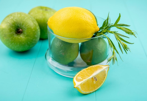 Top view of green and yellow lemons on a glass bowl with green apple on blue surface