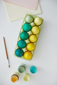 Top view of green and yellow painted easter eggs in crate arranged in minimal composition with paint brush on white background, copy space
