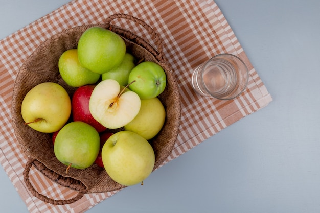 Top view of green yellow red apples in basket and glass of water on plaid cloth and gray background