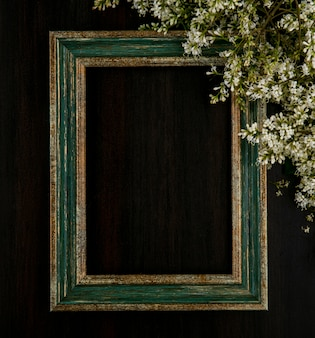 Top view of greenish gold frame with flowers on a black surface