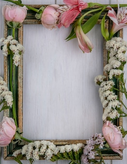 Top view of greenish gold frame with light pink flowers on a gray surface