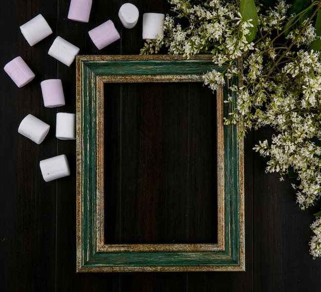 Top view of greenish gold frame with marshmallows and flowers on a black surface