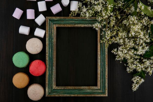 Vista dall'alto della cornice oro-verdastra con marshmallow macarons e fiori su una superficie nera
