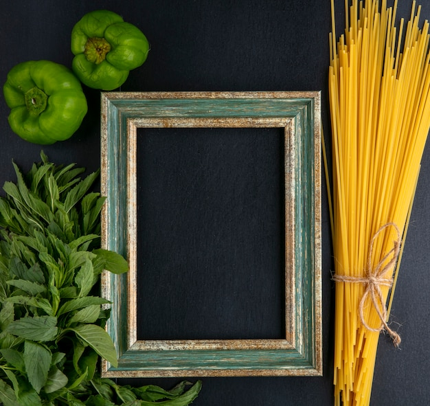 Top view of greenish-gold frame with raw spaghetti mint and bell pepper on a black surface