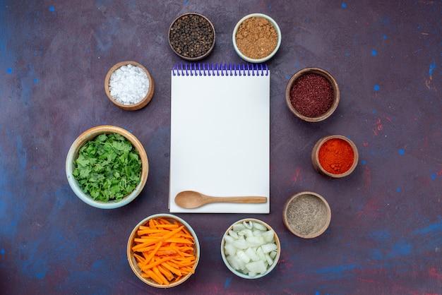 トップビューグリーンと調味料、スライスした玉ねぎとダークデスクのメモ帳サラダフードミール野菜スナック
