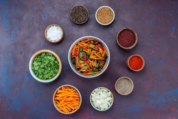 トップビューグリーンと調味料、スライスした玉ねぎとダークデスクのサラダサラダミール野菜スナック