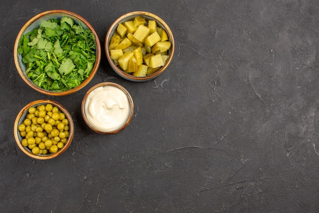 Top view of greens and beans with pickles on grey surface