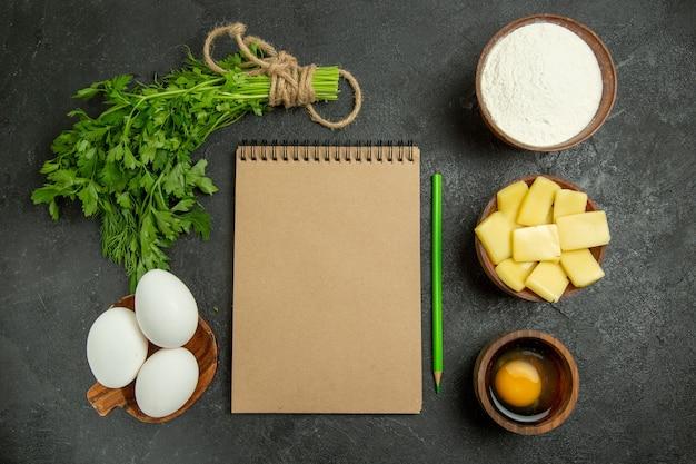 Vista dall'alto verdure e uova con formaggio e farina su uno spazio grigio