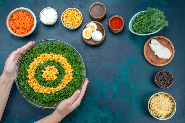 Вид сверху салат из зелени с кукурузой вместе с нарезанной морковью и яйцами на темно-синем столе.