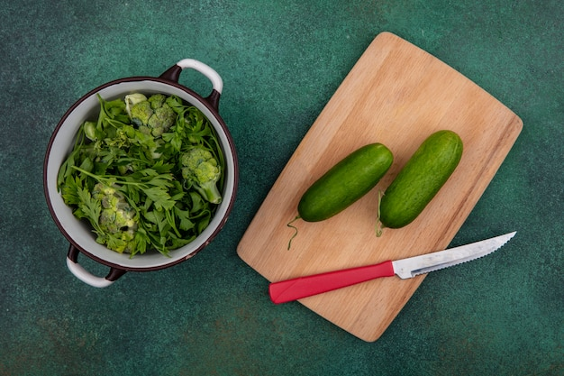 Top view greens in a saucepan with cucumbers on a cutting board with a knife on a green background