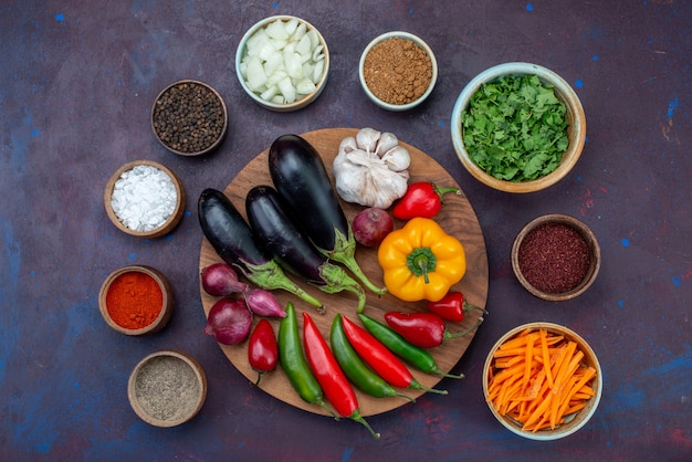 Vista dall'alto di verdure e condimenti con cipolle affettate e verdure fresche sullo spuntino di verdure del pasto dell'insalata della scrivania scura