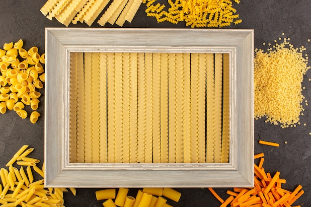 A top view grey photo frame along with different formed yellow raw pasta isolated on the dark