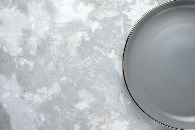 Vista dall'alto della piastra grigia vuota sulla scrivania grigio chiaro, cucina piatto