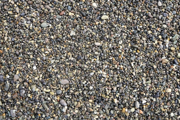 Top view of grey small wet pebble stones at sea beach