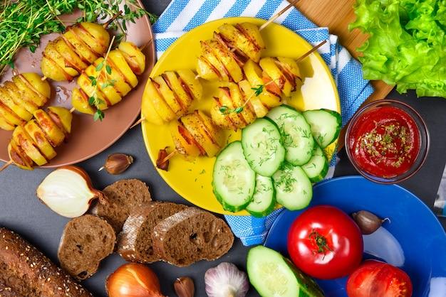 トップビュー:木の棒でベーコンとポテトケバブをグリルします。材料。野菜