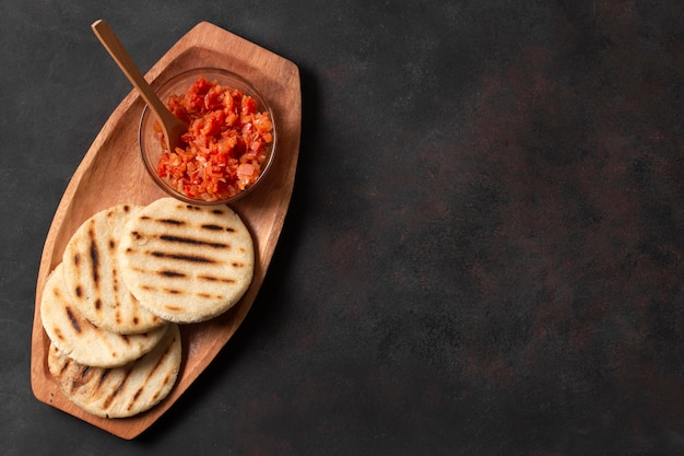 Top view grilled arepas with tomatoes