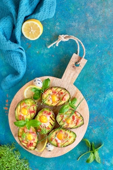Top view on grilled avocado boats with bacon and egg, flat lay on turquoise background