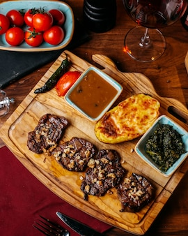 Top view of grilled beef meat with baked potato and sauce on a wooden board