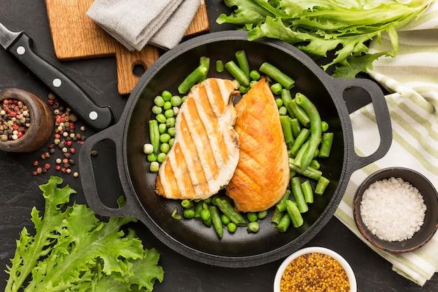 Вид сверху жареный цыпленок и горох в сковороде с приправами