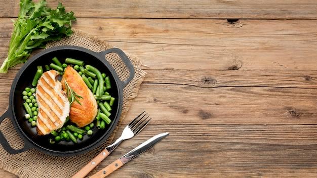Вид сверху жареной курицы и гороха в сковороде со столовыми приборами и копировальным пространством