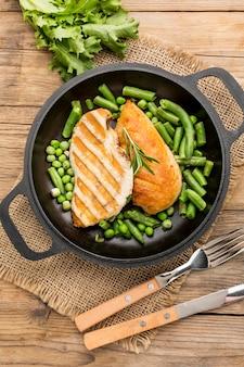 Вид сверху курица-гриль и горох в сковороде со столовыми приборами