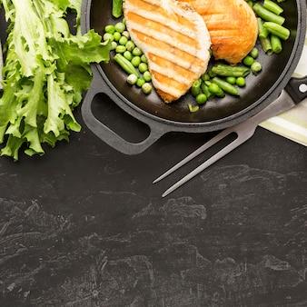 Вид сверху жареный цыпленок и горох в сковороде с салатом и копией пространства