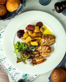 Вид сверху жареная куриная грудка с жареным картофелем и каштанами и овощным салатом на тарелке