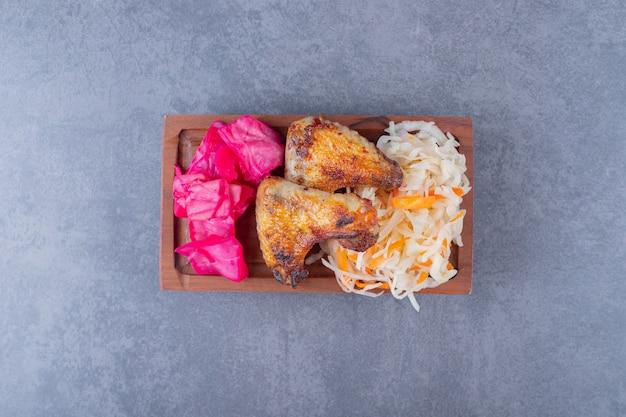 Top view of grilled chicken drumsticks with sauerkraut on wooden board.